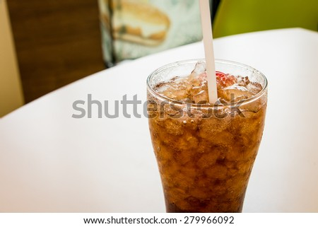 Glass of cola with straw and ice on table - stock photo