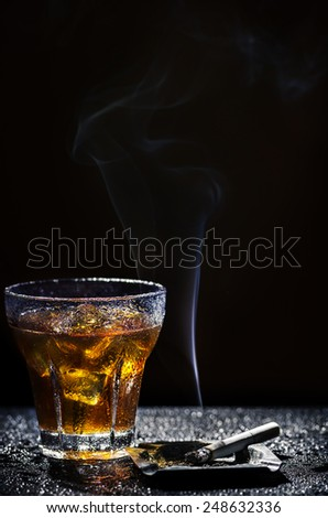 Glass of cold alcohol drink and cigarette over black background - stock photo