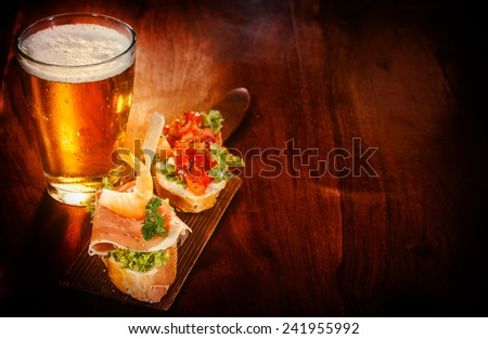 Glass of cold beer with delicious tapas topped with shrimp, parma ham and tomato on baguette served on a wooden bar or pub counter for tasty snacks - stock photo