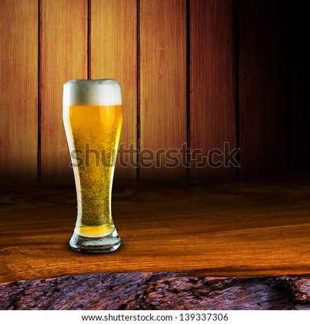 Glass of cold beer with foam on wood table with wood background