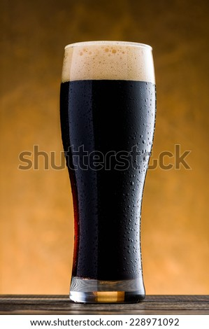Glass of cold dark beer on wooden table - stock photo
