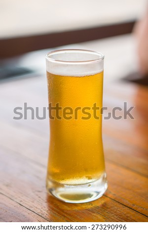 Glass of cold light beer on table in restaurant - stock photo