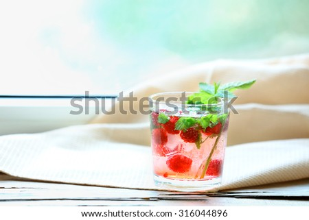 Glass of cold refreshing summer drink with berries and ice cubes on table close up - stock photo
