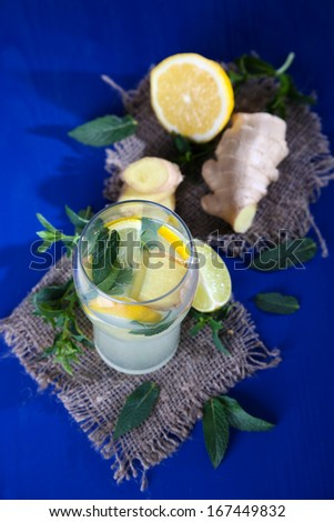 Glass of cold tea with ginger on sackcloth on blue table
