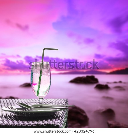 Glass of cold water on dining table with lone exposure fancy colorful seascape sunset background - stock photo