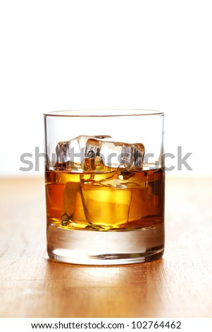 Glass of cold whiskey on wooden surface - stock photo