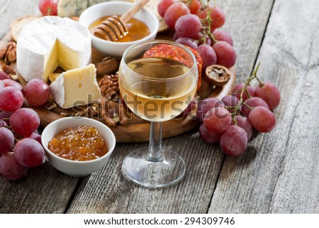 glass of cold white wine and snacks on a wooden background, horizontal - stock photo
