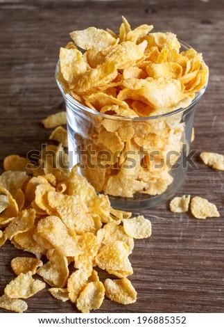 glass of cornflakes on wood - stock photo