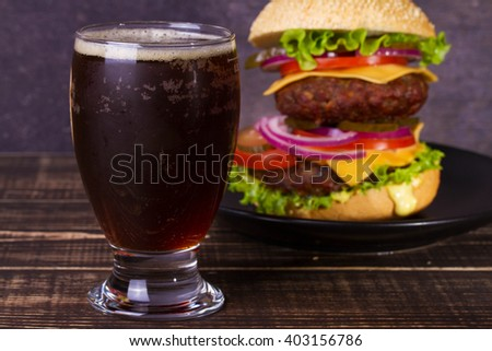 Glass of Dark Beer and  Delicious Burger With Beef, Tomato, Cheese, Lettuce and Onion - stock photo