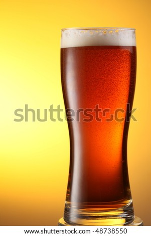 glass of dark beer on a yellow background - stock photo