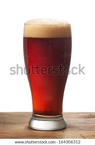 glass of dark beer on wooden table - stock photo