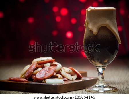 Glass of dark beer, sausages and sliced onion - stock photo