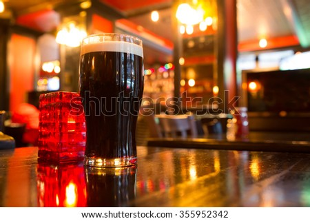Glass of dark beer with candle in pub setting