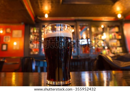 Glass of dark beer with candle in pub setting - stock photo