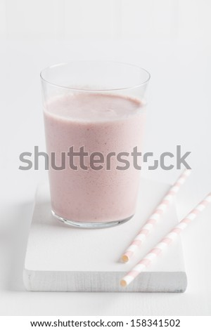 Glass of delicious strawberry smoothie served on white table with two pink drinking straws. Taken on white background.