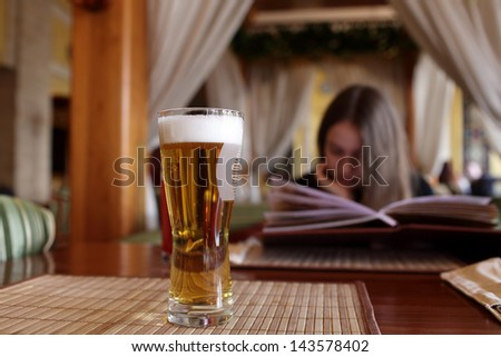 Glass of draught beer on a table in the restaurant - stock photo
