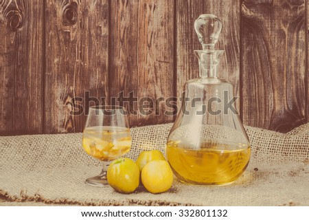 Glass of drink and carafe of alcohol tincture with quince fruits, vintage photo. - stock photo