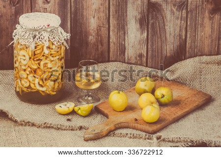 Glass of drink and jar of alcohol tincture with cutted quince fruits on a wooden table covered with sackcloth. - stock photo