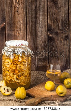 Glass of drink and jar of sliced quince fruits on a wood background. - stock photo