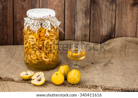 Glass of drink with quince fruits. - stock photo