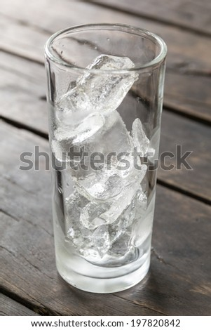 Glass of empty water with ice on the wooden table - stock photo