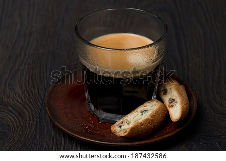 glass of espresso and biscotti with raisins, close-up - stock photo