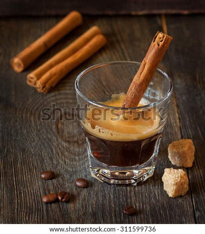 Glass of espresso coffee with cinnamon stick. - stock photo
