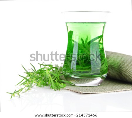 Glass of estragon drink on napkin isolated on white