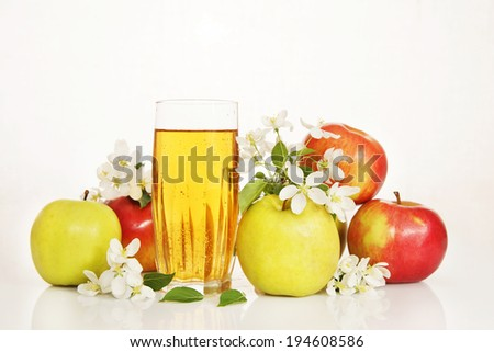 Glass of fresh apple juice with ripe apples and white flowers - stock photo