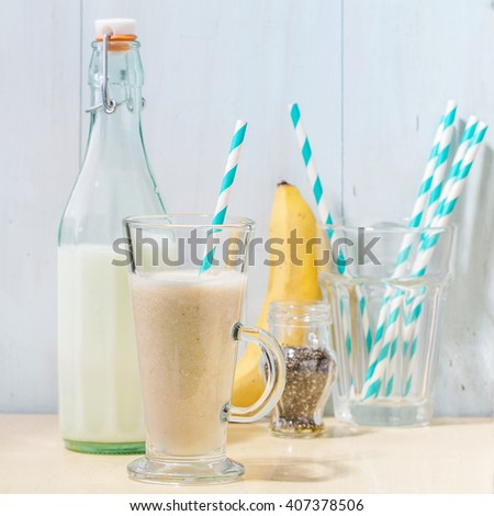 Glass of fresh Banana smoothie with retro cocktail tube, served with bottle of milk, banana and chia seeds over white wooden table. Rustic style. Square image - stock photo