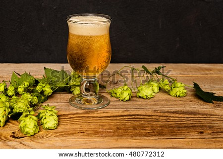 Glass of fresh  beer and hop cones on wooden table