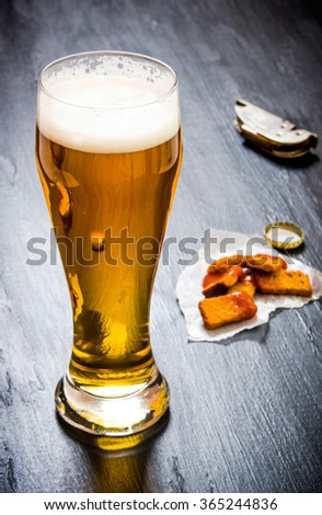 Glass of fresh beer on a black wooden background. - stock photo