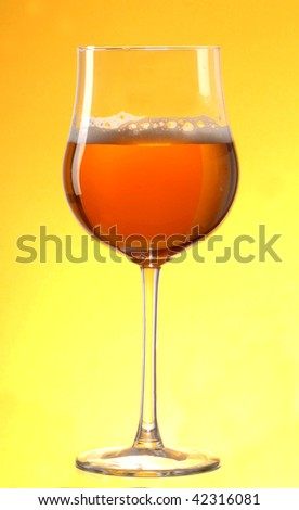 Glass of fresh beer on yellow