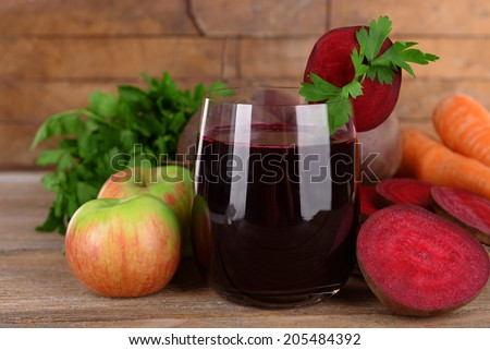 Glass of fresh beet juice and vegetables on wooden background - stock photo