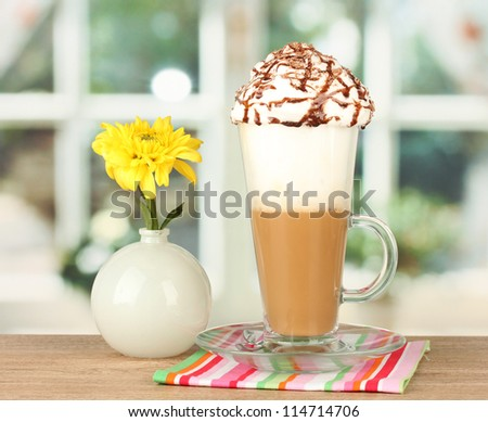 glass of fresh coffee cocktail and vase with flower on wooden table close-up - stock photo