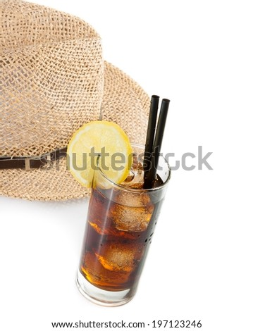 glass of fresh coke with straw in front of summer hat on white background and space for text, summer time - stock photo
