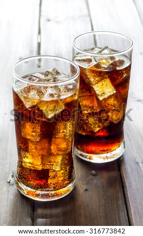 Glass of fresh cola or soda drink with ice cubes. - stock photo