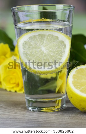 Glass of fresh cold mineral water with a slice of fresh lemon for a tangy taste on a table with yellow roses in a healthy diet and lifestyle concept - stock photo