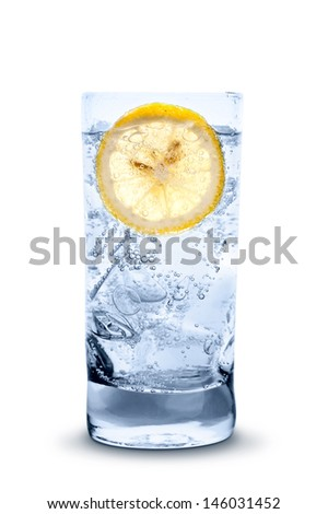 glass of fresh cool transparent water with ice and lemon - stock photo