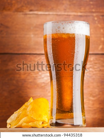 glass of fresh golden beer with potato chips
