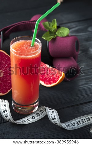 Glass of fresh grapefruit juice, measuring tape and dumbbells on wooden table. Drink for dieting. Selective focus. - stock photo
