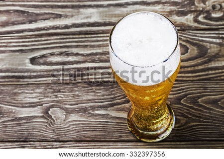 glass of fresh lager beer on a wooden table. focus on Foam - stock photo