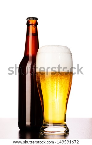 glass of fresh lager beer with bottle cut out from white - stock photo
