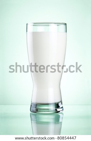 Glass of fresh milk on green background - stock photo