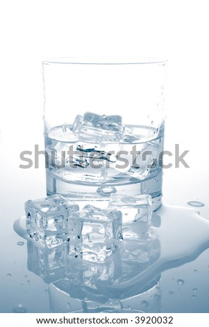 Glass of fresh mineral water with ice cubes reflected on wet background