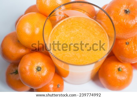 glass of fresh orange juice and many oranges on a white background