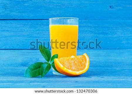 glass of fresh orange juice on a blue background - stock photo