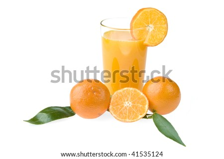Glass of fresh orange juice with two and a half clementines around - stock photo