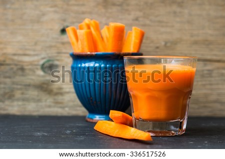 Glass of fresh organic carrot juice and carrot sticks on the wooden background - stock photo