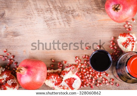 Glass of fresh pomegranate juice, pomegranate seeds and fruits on wooden background. Food frame. Free space for text - stock photo